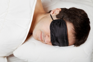 Man with Sleeping mask sleep lying in bed